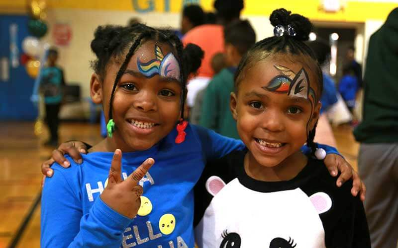 Two girls with faces painted smiling